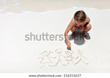 Little girl drawing family picture on a beach