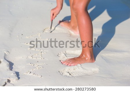 Little girl drawing on sandy beach