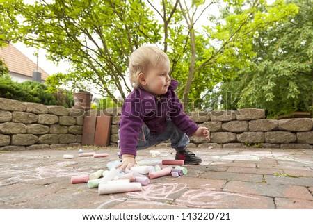 little girl drawing with chalk on ground of the terrace.