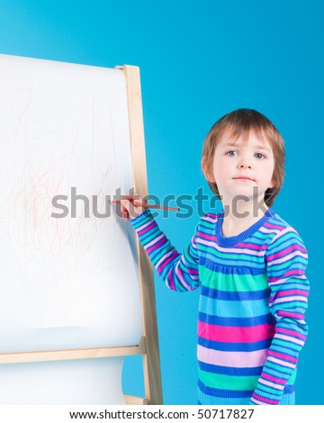 Little girl drawing with her pencil at an easel