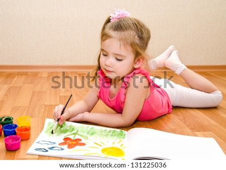 Little girl drawing with paint at home