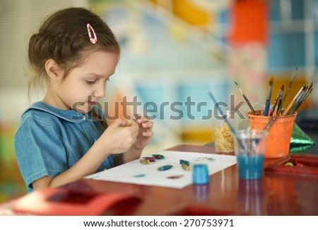 Little girl drawing with paints at home