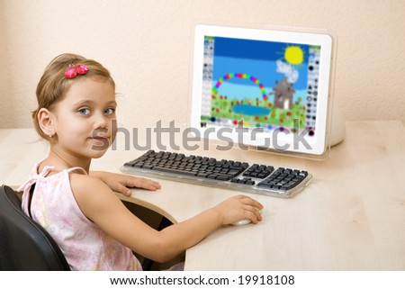Little girl draws at the home computer