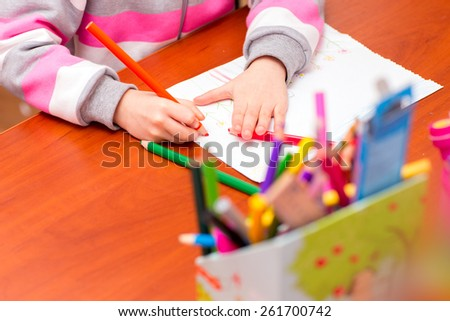 Little girl draws sitting at table in room. #261700742