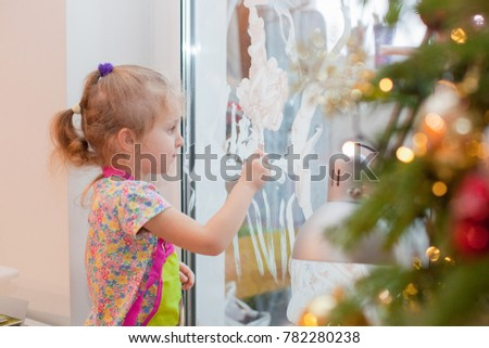 Little girl draws snow pictures on the window with stencil and white paint