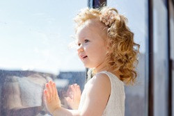 little girl dreamily looks out the window. the sun illuminates her face, flare. the child is on self-isolation and has no opportunity to walk on the street.quarantine due to covid-19