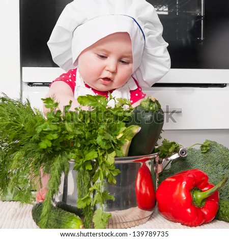 little girl dressed as a chef preparing a meal at home in the kitchen