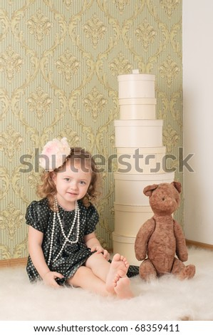 Little girl dressed as a retro doll sits on the floor with a toy