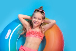 Little girl dressed in a swimsuit lying on an inflatable color ring on yellow background.
