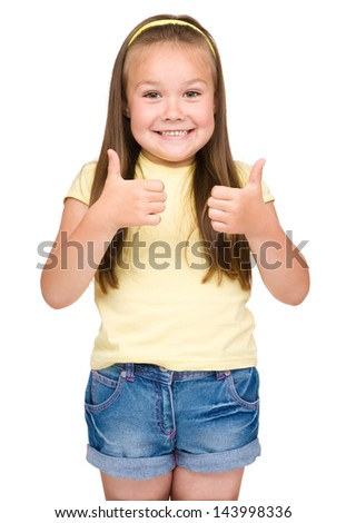 Little girl dressed in blue is showing thumb up gesture using both hands, isolated over white