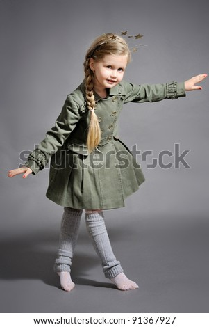 little girl dressed in the New Year on a gray background