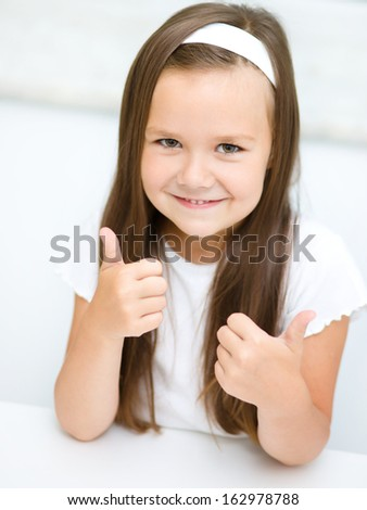 Little girl dressed in white is showing thumb up gesture using both hands