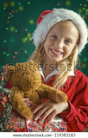 Little girl dressed up as Santa on green background
