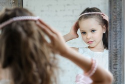 Little girl dresses up front of the mirror. Cute princess in beautiful dress and necklece.