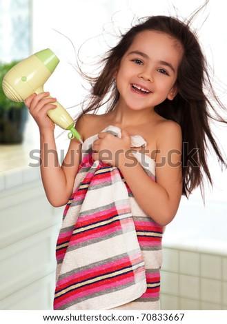 Little girl dries hair after bathing in bathroom