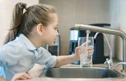 Little girl drinking from water tap or faucet in kitchen. Pouring fresh drink. Healthy lifestyle. Water quality check concept. World water monitoring day. Environmental  pollution problem