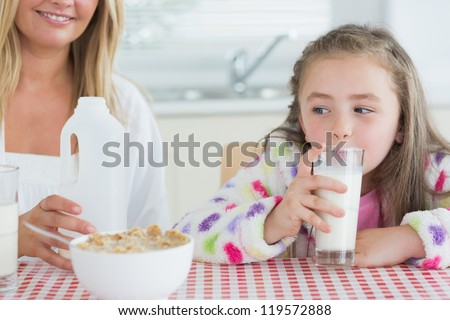 Little girl drinking milk at the kitchen