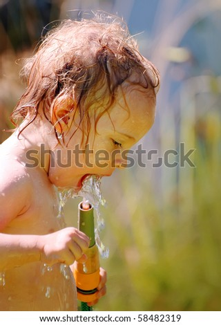 Little girl drinking water from a hose