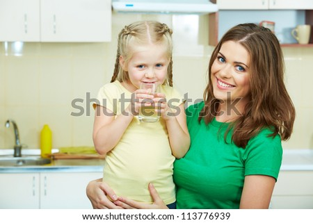 Little girl drinking water in kitchen with young mother.