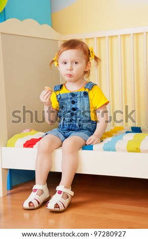 Little girl eat some snacks sitting on the bed in kids birthday