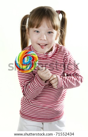 little girl eating a lollipop and sticking out tongue
