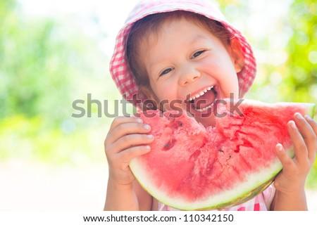little girl eating a ripe juicy watermelon in summertime