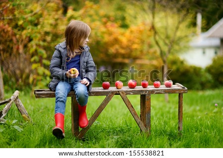 Little girl eating an apple on a wooden bench on autumn day #155538821