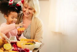 Little Girl Eating  and smile Thanksgiving Celebration Concept. grandmother and granddaughter eating  and smile  at freshly prepared turkey for thanksgiving dinner.
