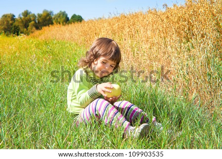 Little girl eating apple near oat field
