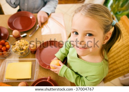 Little girl eating breakfast or dinner with her family