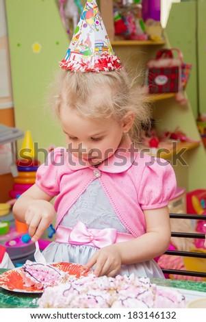 little girl eating cake on her birthday party