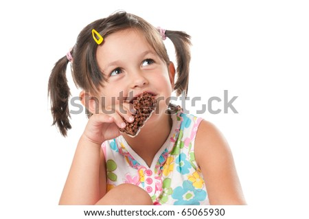 Little girl eating cereal bar for snack isolated on white background