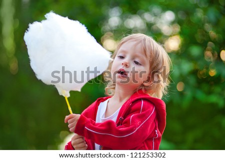 Little girl eating cotton candy in the park in spring