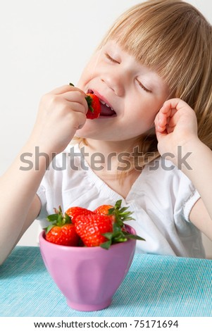 Little girl eating delicious ripe strawberries, bowl in front of her.