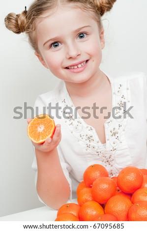 Little girl eating fresh  mandarin