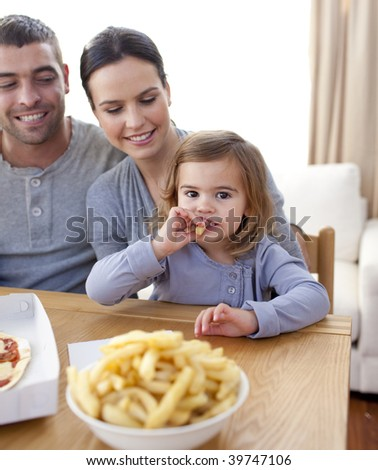 Little girl eating fries and pizza at home with her parents