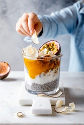 Little girl eating healthy tropical fruit chia pudding with granola, mango, passion fruit and coconut chips in a glass jar. Vegan healthy breakfast, clean eating.