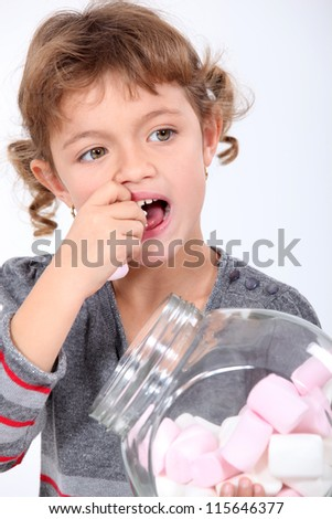 Little girl eating marshmallows
