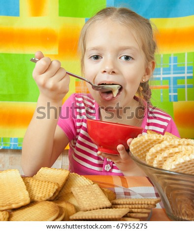Little girl eating   milk dessert from  dish at kitchen