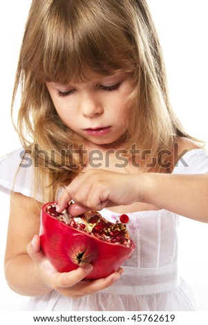 little girl eating pomegranate; closeup
