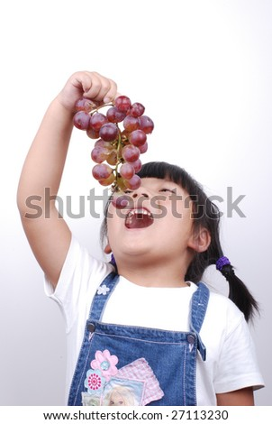 Little girl eating red grape