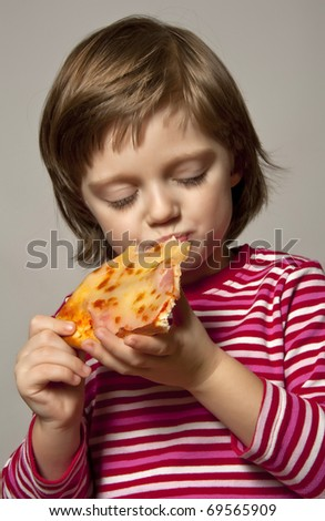 little girl eating slice of pizza