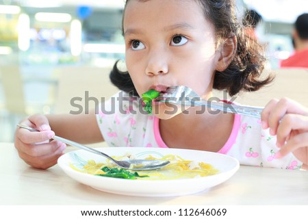 Little girl eating vegetable  - healthy food concept