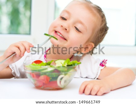 Little girl eating vegetable salad