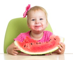 Little girl eating watermelon at table
