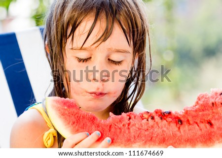 Little girl eating watermelon in very hot summer day