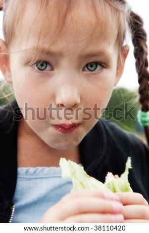 Little girl eats a sandwich - stock photo
