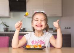 Little girl eats colorful dumplings. Coronavirus quarantine concept. Stay at home.