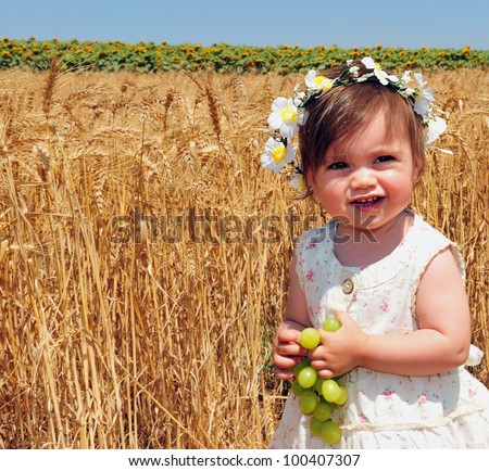 Little girl eats fresh green grapes during the Jewish holiday, Shavuot in Israel.