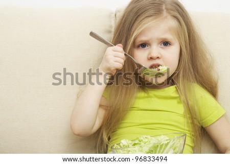 little girl eats green vegetable meal